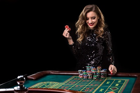 Woman playing in casino. Woman stakes piles of chips playing rou Foto de archivo