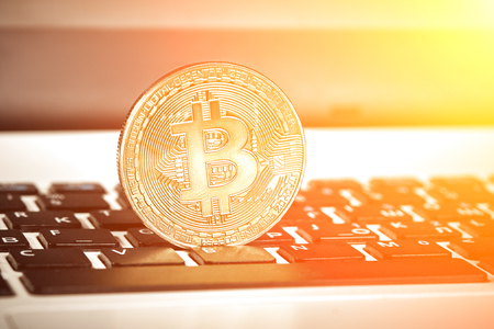 Coin crypto currency bitcoin lies on the keyboard background theme gold exchange pyramid for money due to rise or fall exchange rate close up. Sun flare Stock Photo