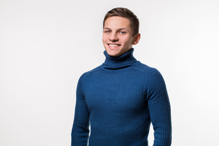 Studio shot of young man wearing blue turtleneck sweater against