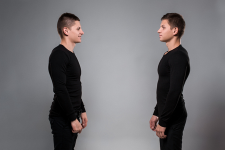 Portrait of young twin brothers standing face to face on gray ba