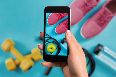 Female hand with a smartphone makes a photo fitness equipment on blue background