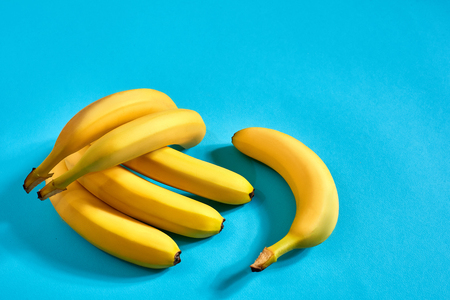 Fresh bananas close up on bright blue background. Flat lay. Summer concept. Stock Photo