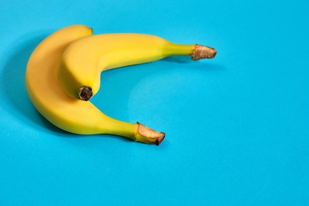 Fresh bananas close up on bright blue background. Flat lay. Summer concept. Still life. Copy space