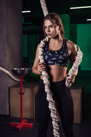 Shot of an attractive female crossfit athlete with a rope at the gym.
