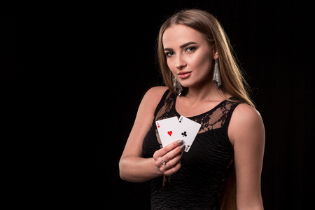 Young beautiful woman playing in casino. Girl holding the winning combination of poker cards. Two aces Reklamní fotografie