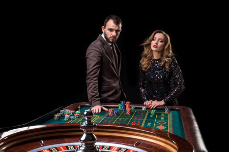 Man with woman playing roulette at the casino.