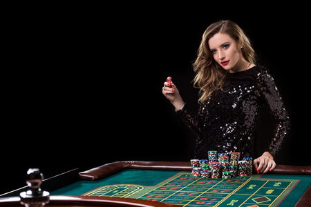 Woman playing in casino. Woman stakes piles of chips playing roulette