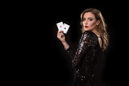 Jeune femme tenant des cartes contre un fond noir Banque d'images - 94134841