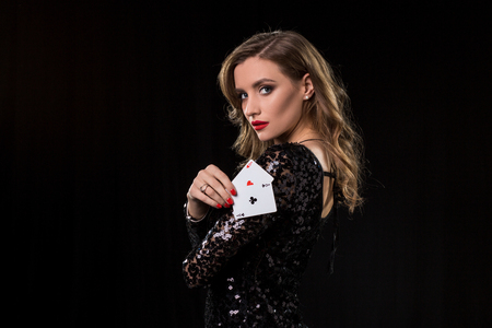Young woman holding playing cards against a black background