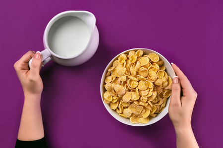 Food and people concept - hands of woman eating cereals for breakfast and pouring milk on the colorful background. Purple background, top view. Copy space. Still life. Flat lay