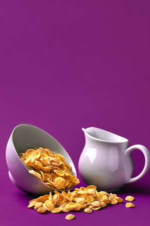 Bowl with corn flakes, jug of milk on purple background. oncept of a healthy breakfast. Copy space. Still life. Flat lay Stock Photo