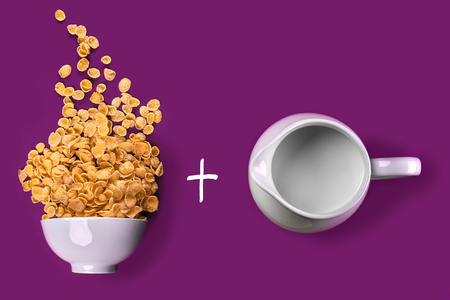 Bowl with corn flakes, jug of milk on purple background. oncept of a healthy breakfast