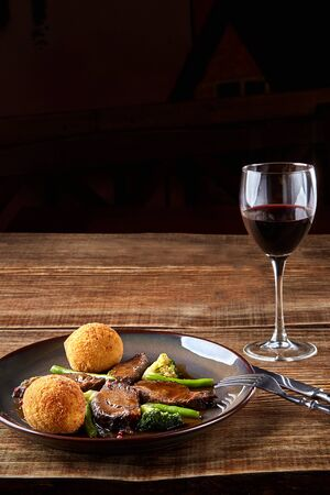 Stewed beef with vegetables and a glass of red dry wine on wooden table, close up. Hot Meat Dishes. Still life. Copy space. Flat lay. Concept restaurant menu Stock Photo