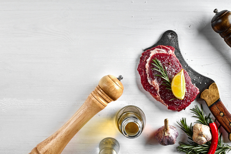 Fresh raw steaks with herbs, garlic, olive oil, pepper, salt, rosemary and a kitchen ax on white background. Top view. Copy space. Still life. Flat lay