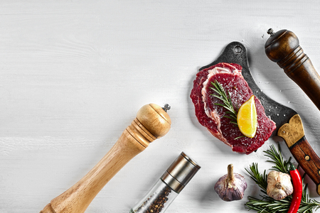 Fresh raw steaks with herbs, garlic, olive oil, pepper, salt, rosemary and a kitchen ax on white background. Top view.