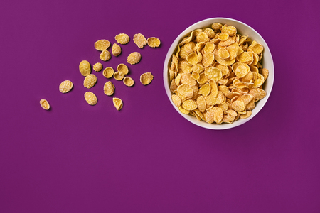 Bowl with cornflakes on the colorful background Foto de archivo