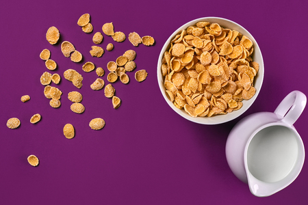 Bowl with corn flakes, jug of milk on purple background, top view