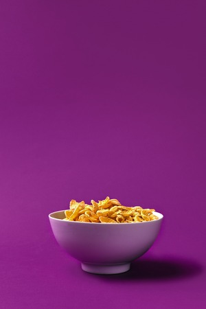 Bowl with cornflakes on the colorful background. Purple background. Copy space. Still life. Flat lay