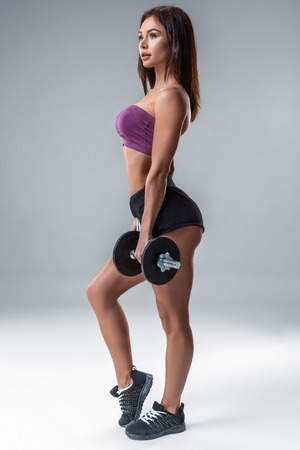 Studio portrait of a sporty young woman posing with dumbbell against a gray background