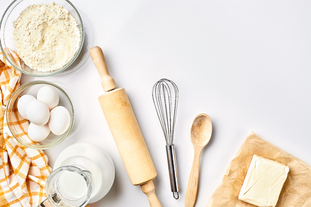 Preparation of the dough. A measurement of the amount of ingredients in the recipe. Ingredients for the dough: flour, eggs, rolling pin, whisk, milk, butter, cream. Top view, space for text Stockfoto