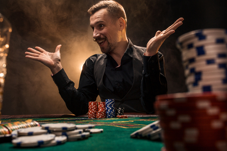 Man is playing poker. A man winning all the chips on the table with thick cigarette smoke. The concept of victory Stock Photo
