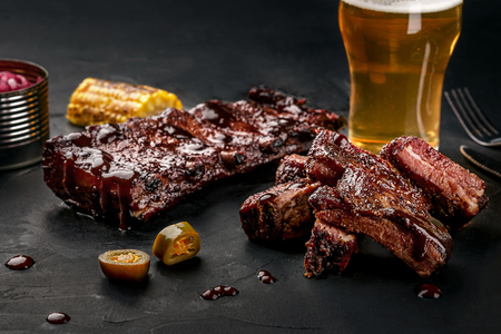 Pork ribs in barbecue sauce and a glass of beer on a black slate dish. A great snack to beer on a dark stone background. Top view with copy space 免版税图像