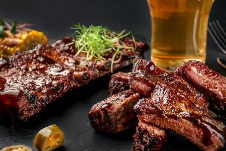 Côtes de porc à la sauce barbecue et un verre de bière sur un plat en ardoise noire. Une excellente collation à la bière sur un fond de pierre sombre. Vue de dessus avec espace copie Banque d'images