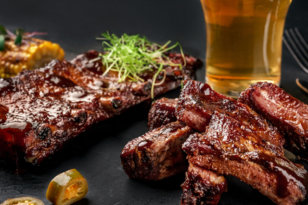Pork ribs in barbecue sauce and a glass of beer on a black slate dish. A great snack to beer on a dark stone background. Top view with copy space Stockfoto