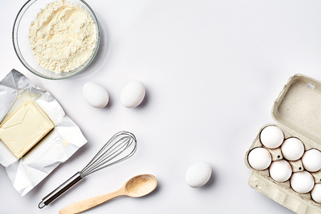 Preparation of the dough. Ingredients for the dough - flour, butter, eggs and various tools. On white background. Free space for text . Top view. Still life. Flat lay Stock Photo