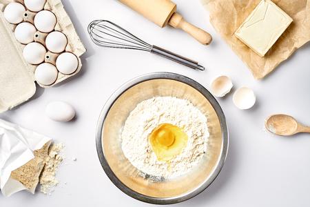 Bakselingrediënten voor gebakje op de witte lijst. Ingrediënten voor het deeg: bloem, eieren, boter. Bovenaanzicht Stilleven. Plat leggen Stockfoto