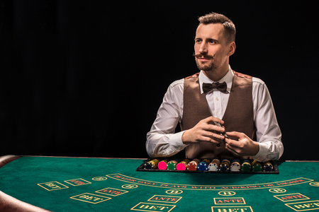 Croupier behind gambling table in a casino. Imagens