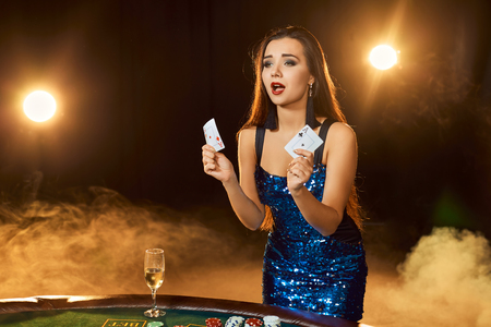 Young beautiful woman poses near poker table in luxury casino. Passion, cards, chips, alcohol, dice, gambling, casino - it is as female entertainment. Smoke background. Standard-Bild - 95359753