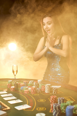 Young beautiful woman poses near poker table in luxury casino. Passion, cards, chips, alcohol, dice, gambling, casino - it is as female entertainment. Smoke background.