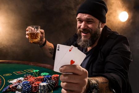 Bebaarde man met sigaar en glas zit aan pokertafel in een casino. Gokken, speelkaarten en roulette. Stockfoto