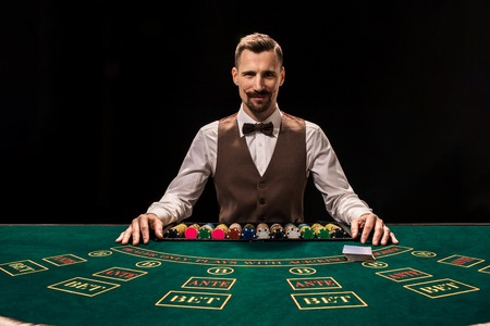 Portrait of a croupier is holding playing cards, gambling chips on table. Black background