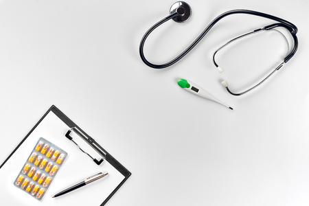Stethoscope in the office of doctors.Top view of doctors desk table, blank paper on clipboard with pen. Copy space. Designers blank
