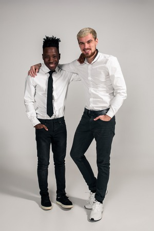 Joyful relaxed african and caucasian boys in white and black office clothes laughing and posing at white studio background with copy space Stock Photo