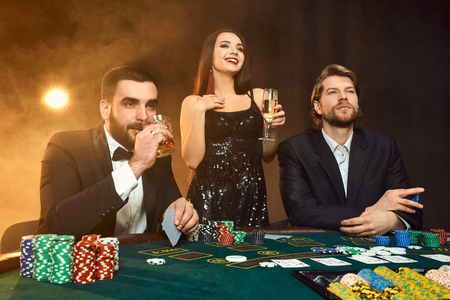 Group of young rich people is playing poker in the casino Stock Photo