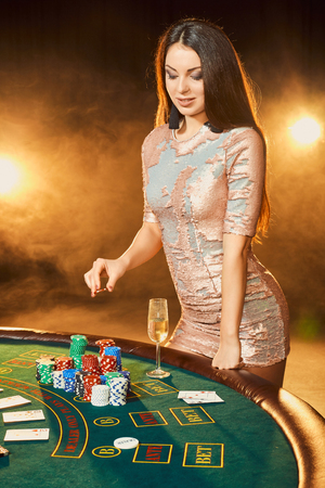 Gorgeous young woman in evening dress standing near poker table with glass of champagne
