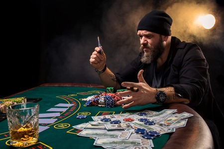 Man is playing poker. Emotional fail in game, game over for card player, man very angry with foolish choices, losing all the chips on bank. Stock Photo