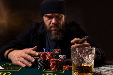 Man is playing poker. Emotional fail in game, game over for card player, man very angry with foolish choices, losing all the chips on bank. Imagens