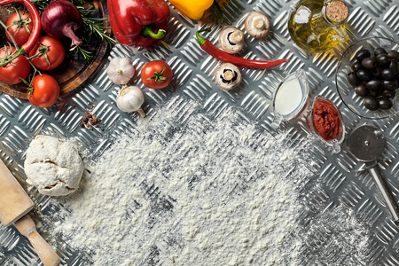 Ingredients and dough for making pizzas with an overhead view on freshly mixed mounds of pastry, a jar of olive oil and pot of tomato sauce, overhead view on metal background. Top view. Flat lay. Still life
