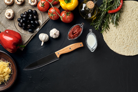 Pizza cooking ingredients. Dough, vegetables and spices on black background. Top view with copy space. Still life. Flat lay