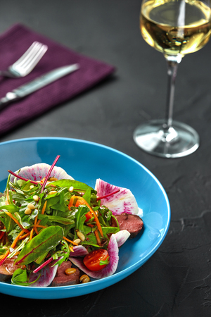 Spicy beef slices meat salad with tomatoes, parsley, radish and salad leaves spinach on black texture background table