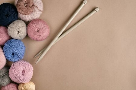 A group of colored balls of yarn and knitting needles on a beige background. Top view. Still life. Copy space. Flat lay Stock Photo