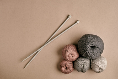 Knitted from a gray yarn sweater and thread for knitting closeup. Knitting as a hobby. Accessories for knitting on a beige background. Top view. Still life. Copy space. Flat lay