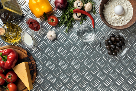Food ingredients and spices for cooking pizza. Mushrooms, tomatoes, cheese, onion, oil, pepper, salt, egg, grater on metal background. Copy space. Top view. Flat lay. Still life Archivio Fotografico