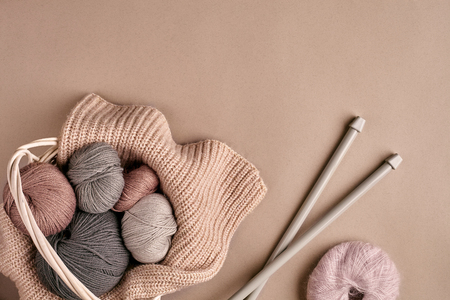 Different colored yarn in basket with knitting needles on a beige background. Top view. Copy space. Still life. Flat lay Фото со стока