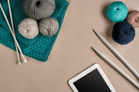 Grey and turquoise knitting wool, knitting needles and a tablet with a black screen on beige background. Knitting as a kind of needlework. Colorful balls of yarn and knitting needles. Top view. Still life. Copy space. Flat lay