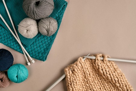 Grey and turquoise balls wool and knitting on needles on beige background. Knitting as a kind of needlework. Colorful balls of yarn and knitting needles. Top view. Still life. Copy space. Flat lay